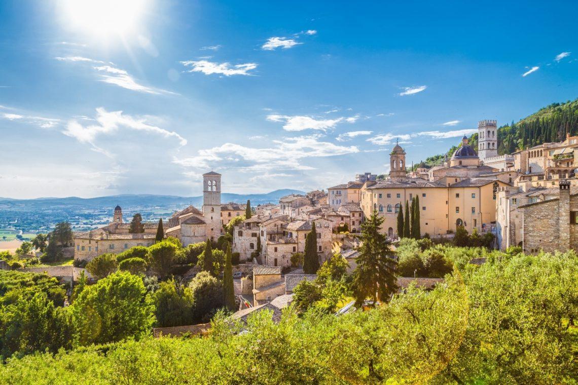 Vista da cidade de Assis em meio à natureza, com a sua arquitetura em pedra e os campanários das igrejas em destaque.