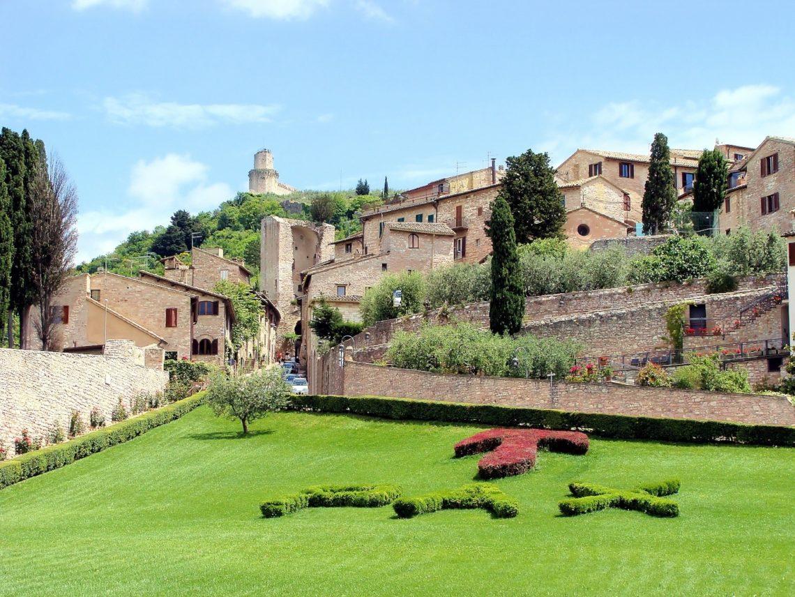 Vista do Jardim da Basílica de São Francisco de Assis, com casas ao redor. Ao fundo e no alto, parte da muralha que circunda o burgo.