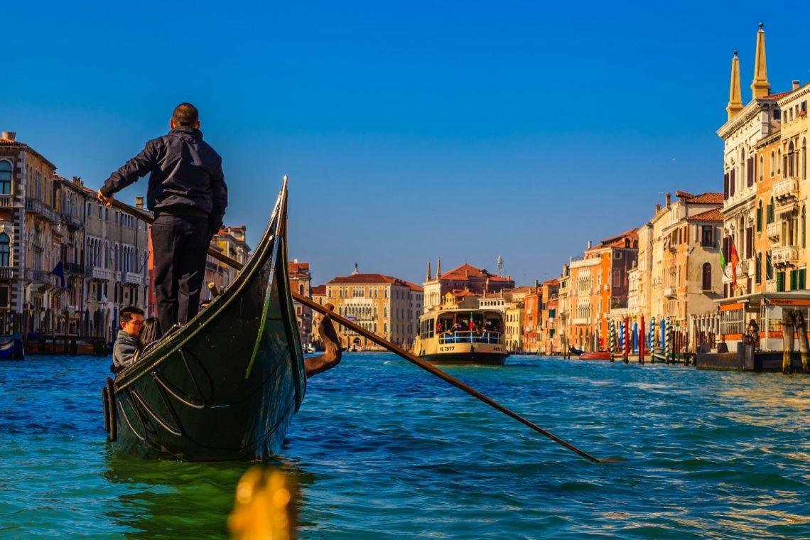 Gondoleiro transporta turistas pelo Canal Grande num dia ensolarado.