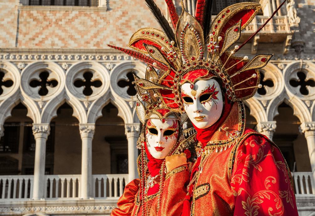 Casal de foliões diante do Palazzo del Doge, com traje e máscaras tradicionais.