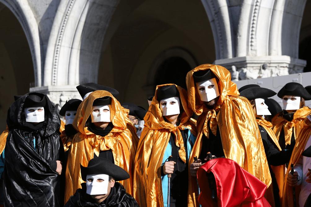 Grupo de amigos vestindo a tradicional Bauta veneziana, composta de chapéu de três pontas (tricorno), manto (tabarro) e máscara (larva).